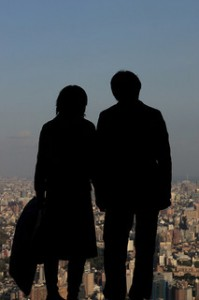 An older couple stands silhouetted against a view of Tokyo