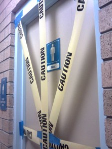 photo showing four angled strips of yellow and black caution tape covering the taupe door of a public toilet with a small sign indicating it is for men.