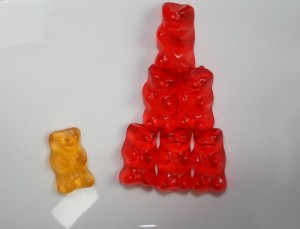 A lone orange gummy bear sits beside six red gummies arranged in a pyramid.