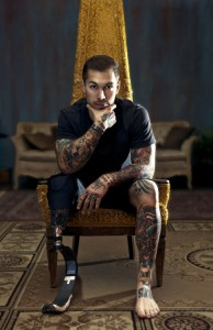 A white man with an athletic build sits in an upholstered chair and looks at the camera while holding his chin in his right hand. His arms and left leg are covered in many colorful tattoos. His right leg is a below-the-knee prosthetic meant for running on.