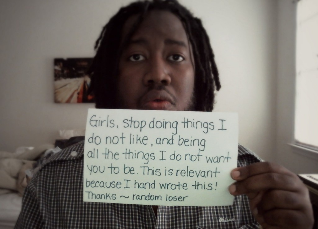 "A black man with dreads looks at the camera while holding a handwritten note. It reads, "" Girls, stop doing things I do not like, and being all the things I do not want you to be. This is relevant because I hand wrote this! Thanks ~ random loser"""