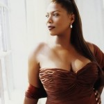 Queen Latifah looks over her shoulder at a window while wearing a brown strapless dress. Her long hair is in a long ponytail swept over her other shoulder.