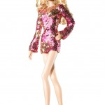 A white-skinned Barbie doll with blond hair wearing a sparkly, pink minidress and high-heeled, gold gladiator sandals.