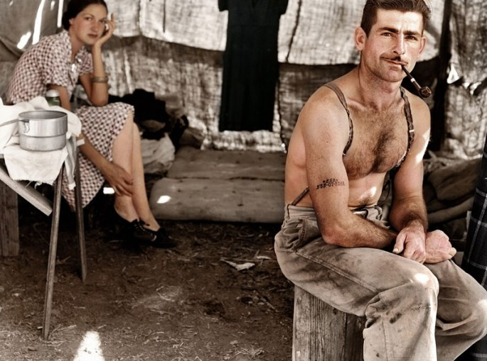 Unemployed Lumber Worker and His Wife, circa 1939. A white man with a thin mustache sits on a stump under a tent smoking a pipe while wearing pants and suspenders and no shirt. A white woman in a patterned dress sits in a chair in front of a mattress on the ground further back in the tent.