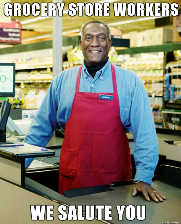 "A black man wearing a red apron stands behind a cash register. The text reads, ""Grocery store workers: we salute you."""