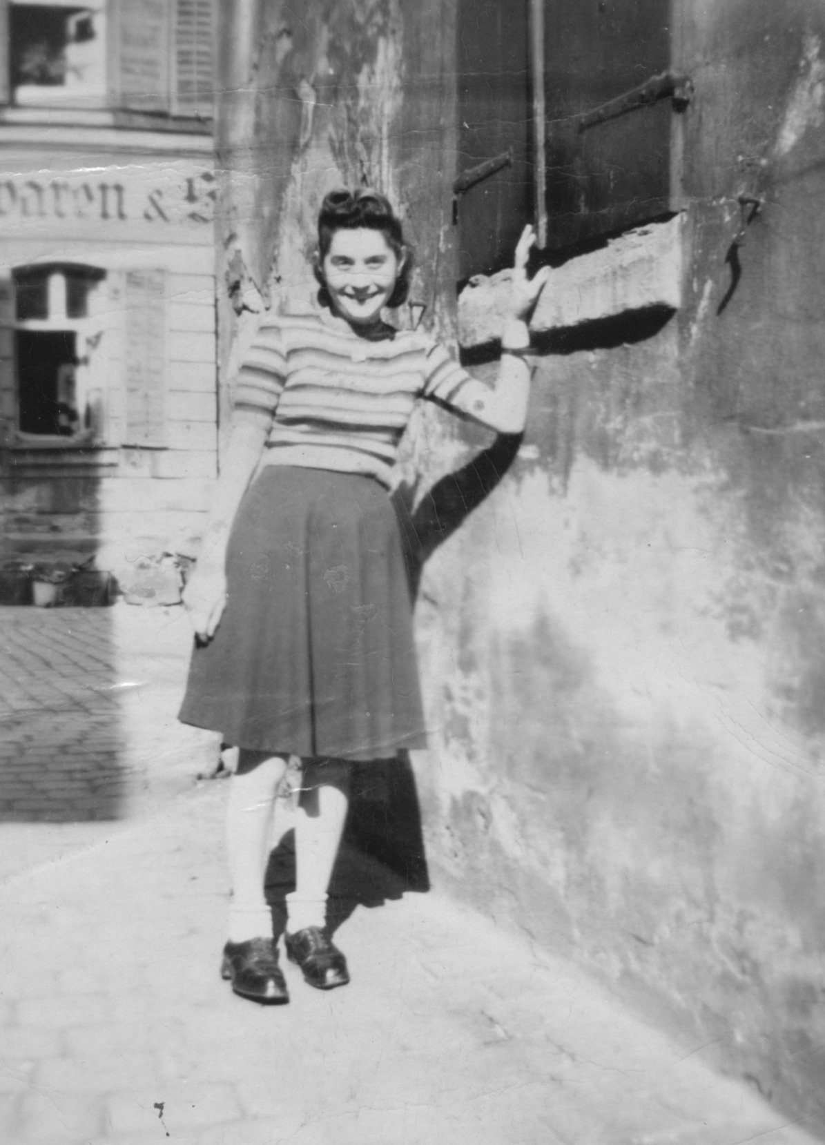 A young Jewish woman with dark hair stands next to an old building and leans against the windowsill while wearing a striped shirt with a solid skirt that reaches her knees. Black & white. 1945