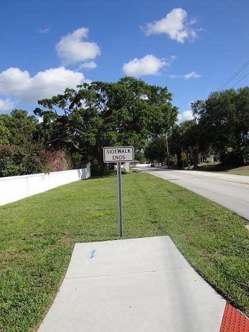 "A color photo of a sidewalk surrounded by green grass. A white sign on a metal post says ""SIDEWALK ENDS"" in black letters."