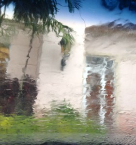 tropical rain obscures the view of a sand colored building with palm trees
