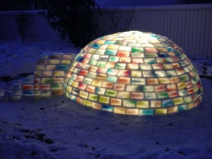 An igloo made from colorful ice bricks and snow mortar is lit from inside at night.