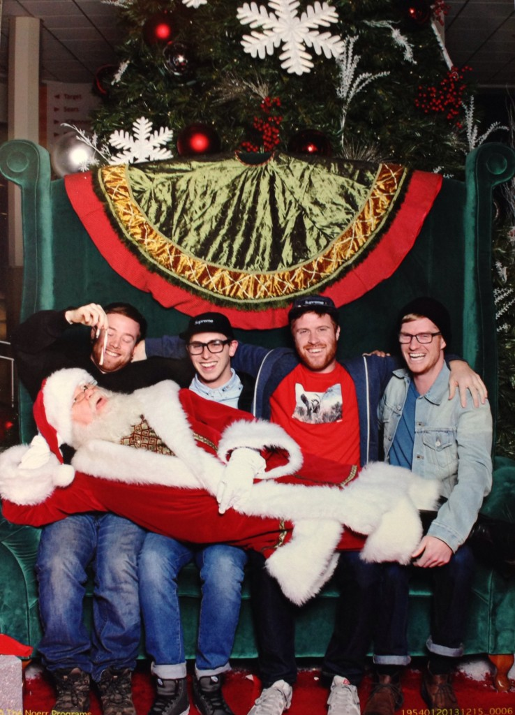 Four white guys sit with Santa laid out along their laps. One of the guys dangles a candy cane over Santa's open mouth.