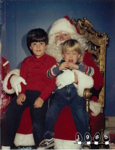 Two white boys sit on the lap of a mall Santa. The five year old with brown hair smiles. The two year old with blond hair is crying and trying to get away.