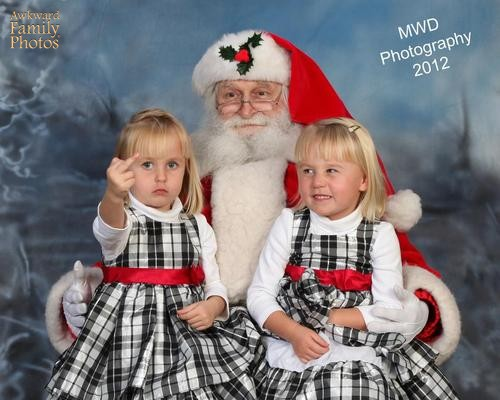 Twin little blond white girls in matching plaid jumpers sit on Santa's lap. One gives the photographer the middle finger.