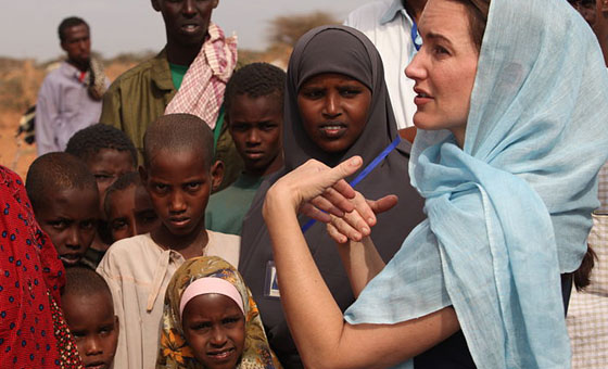 A white woman in a blue headscarf stands in front of a mixed group of black children in Africa. One boy gives the photographer a dubious look.