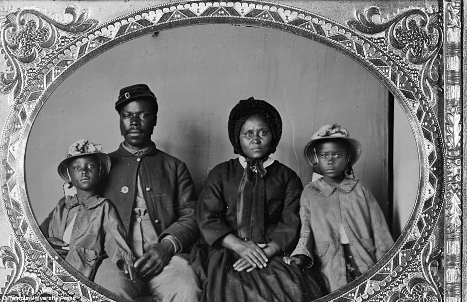 An African American soldier in Union uniform with wife and daughters between 1863 and 1865.