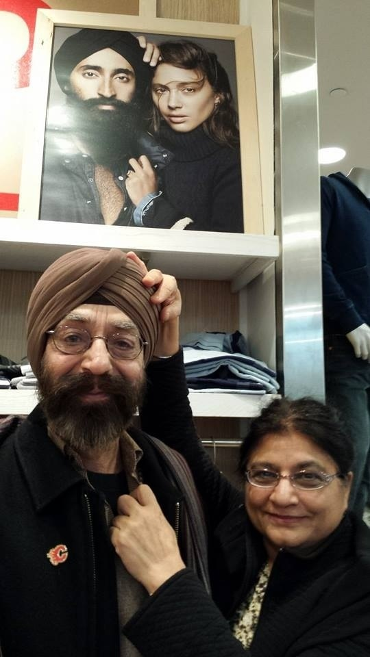 A middle-aged Sikh man wearing a turban emulates the pose of the models in a Gap ad he stands below with his wife.