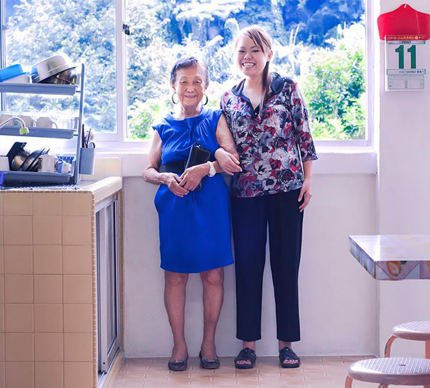 A twenty-something year old woman stands next to her grandmother. The older woman is wearing a bright blue shift dress and flats. The younger woman wears her grandmother's floral patterned shirt, dark blue pants and comfortable shoes.