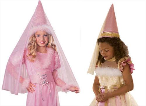 A blond white girl and a dark-haired black girl wear princess dresses and conical hats with a gauzy veil at the tip.