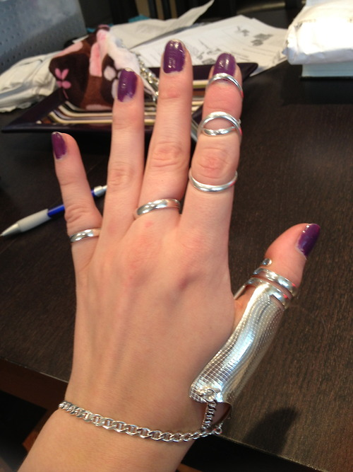 A white woman's hand. The fingernails are a sparkly purple polish and she has a number of silver rings on her fingers and a silver splint on her thumb.