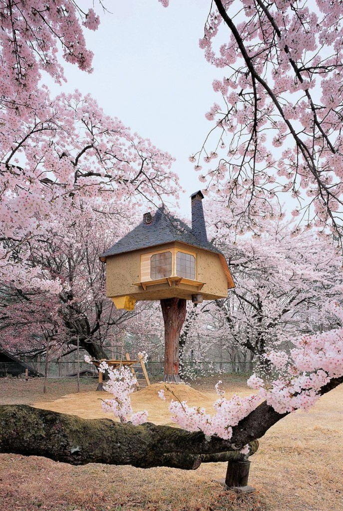 A whimsical, storybook treehouse is on top of a tree trunk and surrounded by blooming cherry trees covered in pale pink flowers.