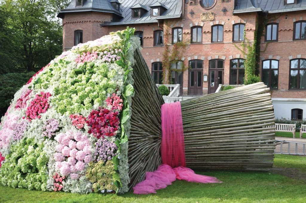 Long, straight, tree branches form the stem and an enormous mound of flowers form the crown of a large art installation that looks like a giantess' bridal bouquet.