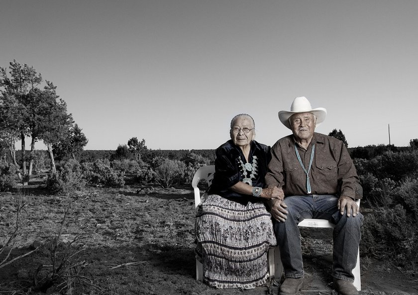An elderly Native American couple sits outside in rural scrubland, holding hands. She wears a long black and white patterned skirt with a black shirt. He wears jeans, a button-down brown shirt, a beaded turquoise necklace and a white cowboy hat.