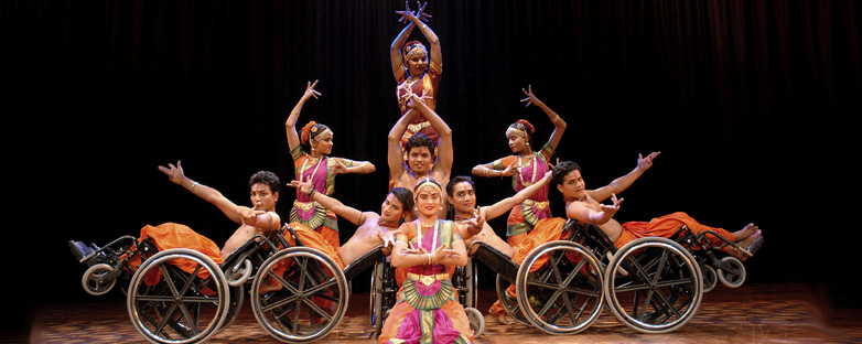 a 9 person Indian dance troupe in pink, orange and green costumes poses onstage. 5 dancers are in wheelchairs and the other 4 are ambulatory.