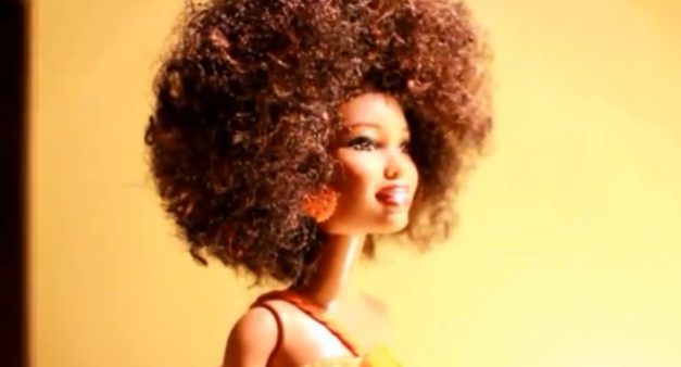A dark skinned Barbie doll with kinky, curly hair done up in an afro.