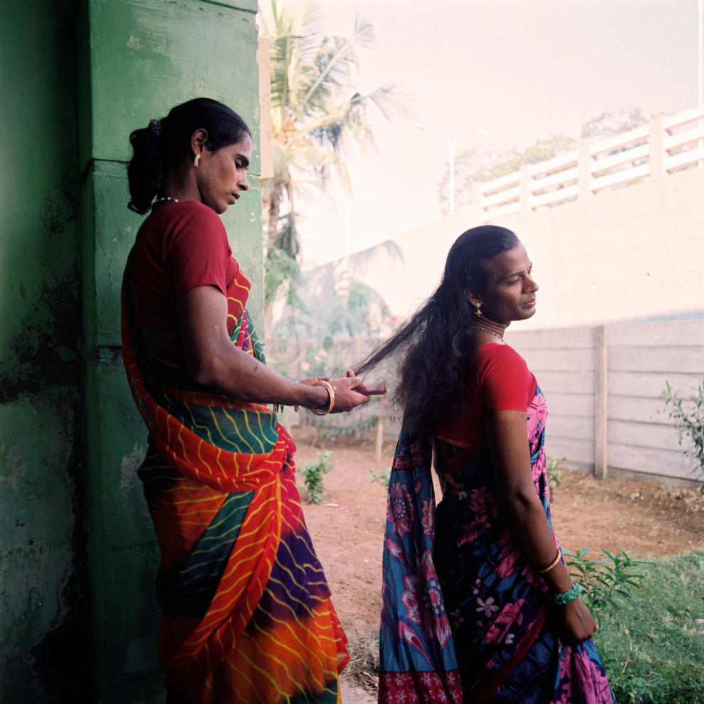 Two masculine-presenting people in colorful saris stand outside while one combs the long, dark brown hair of the other.