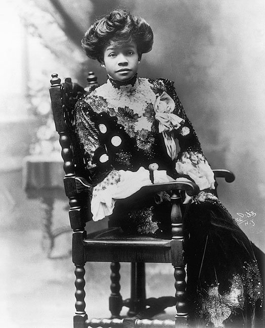 A black vaudeville actress, Aida Overton Walker, circa 1900. She sits in a carved wooden chair wearing a high-necked gown decorated with lace and embroidery and has her hair piled on top of her head.