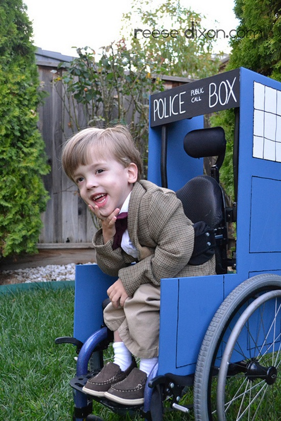 A young white boy wears a brown suit and red bowtie and sits in a wheelchair made to look like the blue TARDIS from Doctor Who