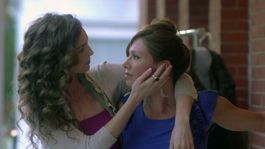 Two white women embrace, one holding the others face in her hand while they stare into each other's eyes