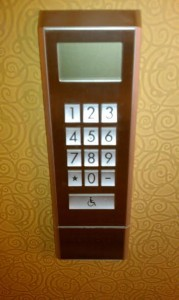 Picture of the elevator number pad at the hotel. It has a grey lcd screen on top, buttons numbered 0-9 below and a button labeled with a wheelchair icon at the bottom.