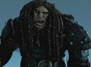 A large animated man with broad features and dreadlocks looms threateningly