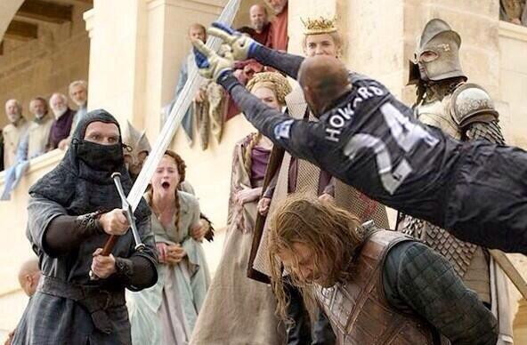 USMNT goalkeeper Tim Howard, wearing  a black kit and white gloves, is photoshopped in a scene from Game of Thrones so he appears to be diving to stop the sword that's about to behead Ned Stark.