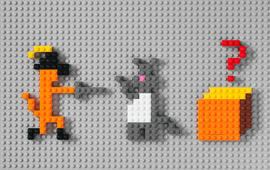 Lego blocks are arranged on a grey background to form three figures. 1. an orange cat wearing boots and a feathered hat, standing on two legs and pointing a sword. 2. A grey cat with a white belly and pink nose. 3. An orange box with a question mark above it.