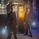Two white men,, one dressed in a suit like the Tenth Doctor and one dressed in jeans, tshirt and leather jacket like the Ninth Doctor, pose in front of a TARDIS while holding sonic screwdrivers.
