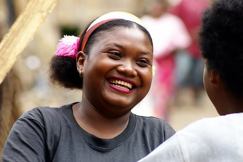 A dark-skinned indigenous Malaysian woman smiles at someone off-camera. She wears a black t-shirt and colorful headband.