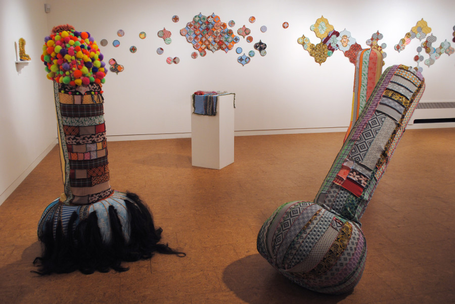 An art gallery with white walls and a shiny wood floor. 5 foot tall phalluses made from colorful strips of fabric sewn together in random intervals stand around the room.