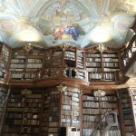 An ornate library with carved wooden shelving, hidden doors, a gallery and an illustrated ceiling.