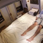 An Asian man in khaki shorts and a blue oxford shirt sits comfortably and watches tv on a double bed during a flight from Singapore to NYC.