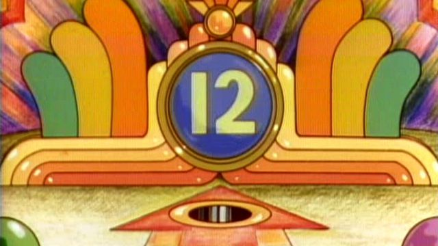 A still from a 1977 Sesame Street video. The number twelve shows in a round window over a pinball hole and is surrounded by bumpers in shades of orange.