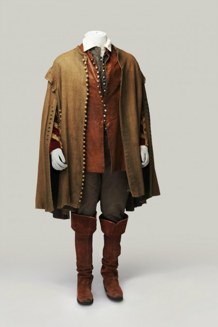 A brown cape lined by tiny buttons from hem to collar in the front and hem to shoulder at the arms. The embroidered arms of a coat peek out on the sides. A red-brown leather waitcoat is buttoned from waist to chest with the rest of the many buttons left undone. Dark brown fitted breeches are tucked into tall brown leather boots with a wide cuff over the knee.