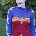 A white woman with dark brown hair, pale skin and bright red lips smiles as she models a sweater in a lush backyard. The body of the sweater is red and gold in the outline of Wonder Woman's corset top. The chest and sleeves are blue, with white stars running from collar to sleeve cuff. The cuffs are gold.