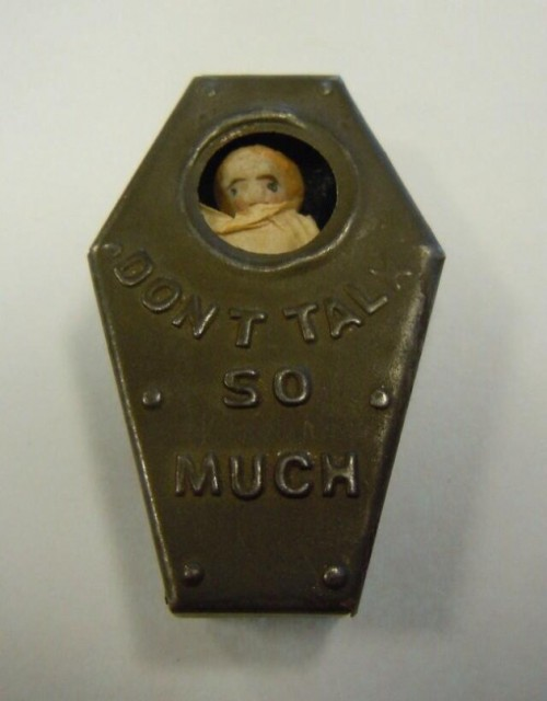 "A Victorian-era antique. A small olive green metal coffin. A glass window reveals the simple face of a small doll. A raised inscription reads ""don't talk so much"""