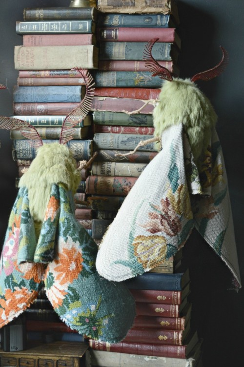 Fuzzy green moths with wings made from vintage needlepoint tapestry climb a set of 19th century books.