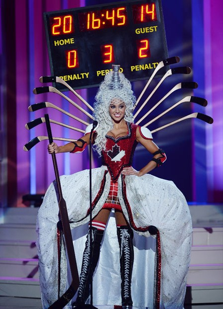 A white woman in a LouisXIV style white curly wig with a Stanley Cup replica on top. Hockey sticks are arranged like angel wings. A sequined red bustier has a black and white maple leaf in the center.  Red and white shoulder and elbow pads are on her bare arms. A White overskirt supported by wide panniers frames a mini skirt that looks like a hockey net and tall black boots laced up to mid-thigh like hockey skates, She holds a tall hockey stick like a staff and there is a scoreboard attached to her headdress somehow. Home team: 20, visitor: 14.