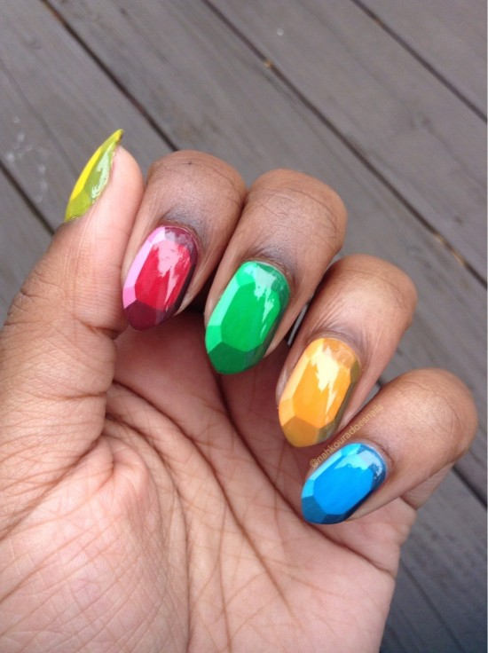 A dark skinned woman's fingernails are painted to resemble the rupee gems from the Zelda video games.