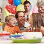A stock photo of a child's birthday party. A white father is flanked by a young son and daughter at a table with a birthday cake on it. A white mother and grandmother look on. In the back, with the balloons, stands a middle-aged white man in a white tank top holding a beer and looking out at the viewer.
