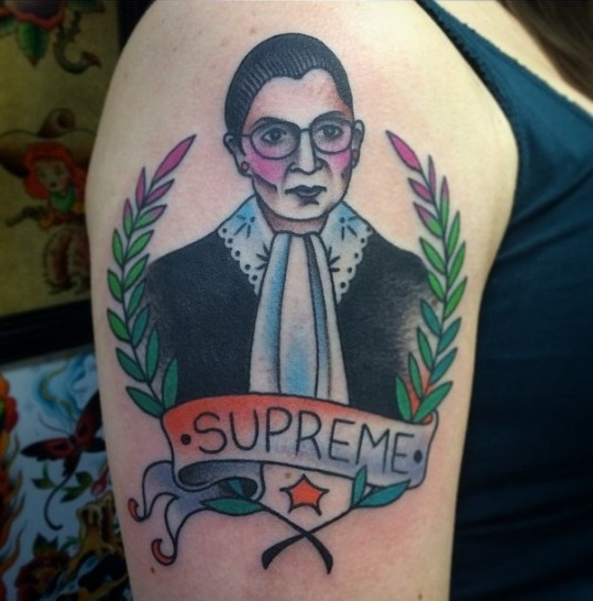 A color tattoo of Ruth Bader Ginsburg from the chest up in her black robe and distinctive lace collar. Laurel frames the sides and SUPREME is written on a scroll below.