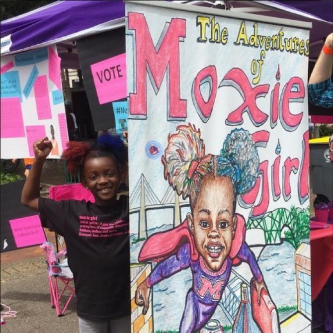a young black girl with afro puffs stands flexing her biceps next to a tall banner with the illustrated cover for her comic The Adventures of Moxie Girl on it
